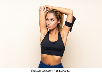 Young sport woman stretching over isolated background