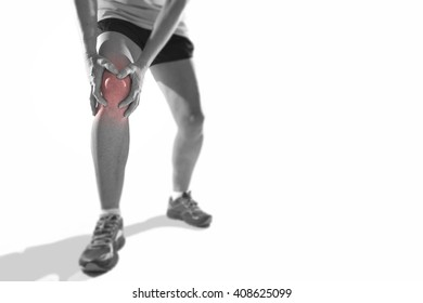 young sport woman with strong athletic legs holding knee with his hands in pain after suffering ligament injury during a running workout training isolated  background in black and white with red spot