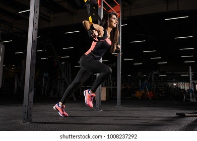 Young sport woman training with TRX suspension strap at fitness club.