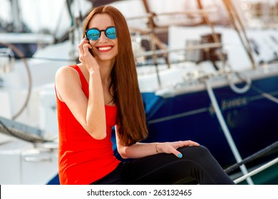Young sport woman using mobile sitting near the yachts at the marine