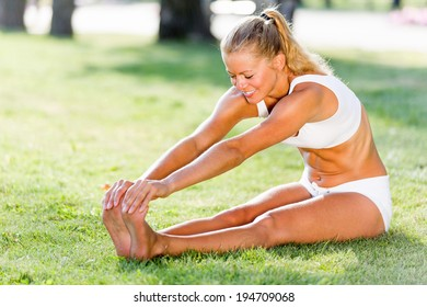 Young sport woman in white stretching in park
