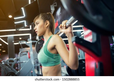 Young sport woman working out with weight lifting in gym. Healthy with fitness and exercise concept.