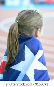 Young sporting fan draped in the Australian flag at an athletics event.