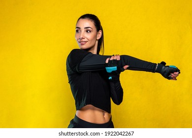 Young sportive attractive caucasian athlete woman posing in black outfit with black and light blue glow gym gloves - Studio shooting with pretty slim sportive brunette doing aerobic stretching
