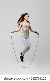 Young sportive beautiful girl doing exercises with jumping rope over white background.