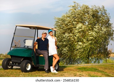 Young sportive couple playing golf on a golf course. Standing near the golfcar