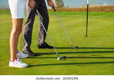 Young sportive couple playing golf on a golf course. Close up