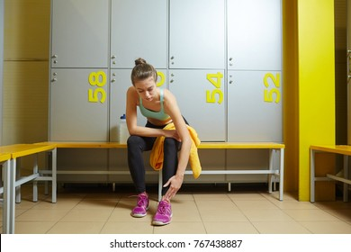 Young sportive female touching her sprained ankle while sitting on bench in dressing-room of sports club