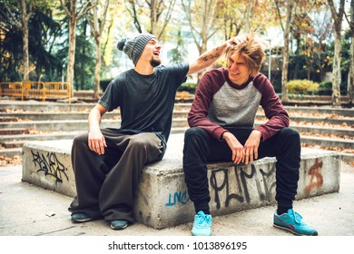 Young sportive friends playing and teasing each other having fun in park during freerunning workout.