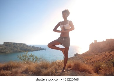Young sportive girl doing yoga in an amazing natural place