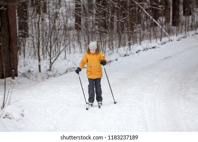 Young sportive girl running on skies in winter road in forest, full-length, copyspace
