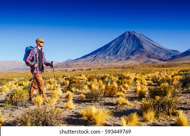 Young sportive hiker trekking near volcanos in Chile.  Lascar volcano. Atacama. Chile. Sport and active life concept