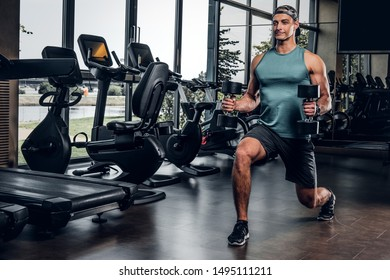 Young sportive man is doing exercises with dumbbells in empty gym club.