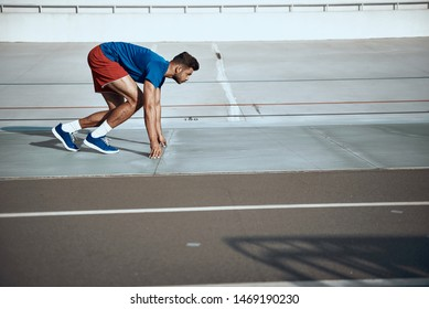 Young sportive man on starting position ready to running at competition