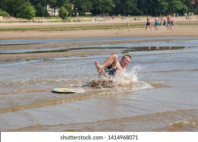 Young sportive man was riding on skim board and falling down suddenly and hurt, injures his leg joints, hand tendon on sunny summer day on sandy beach