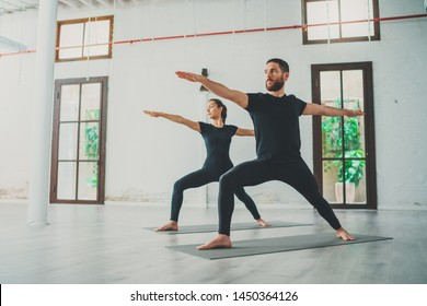 Young sportive man and woman are practicing yoga exercises in the studio. Couple of young sporty people practicing yoga lesson with partner.