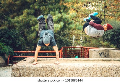 Young sportive men showing tricks and exercises training freerunning in park.