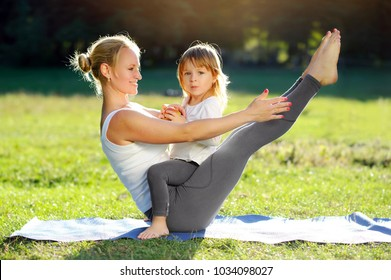 Young sportive mother playing with her little daughter while practicing boat yoga pose