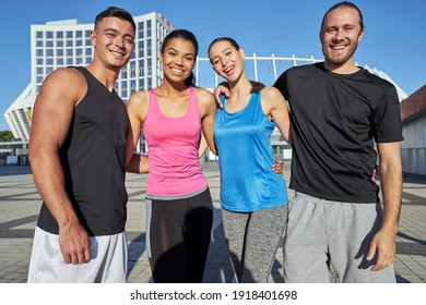 Young sportive people hugging on cityscape background