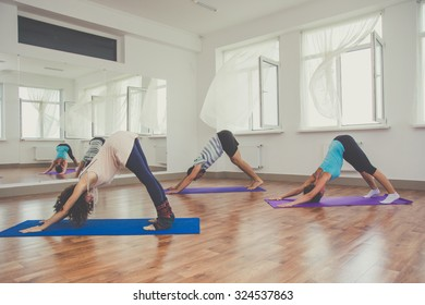 Young sportive trio group boy and two girls are practicing yoga exercises in the studio