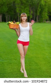 Young sportive woman with basket of fruits after fitness exercise