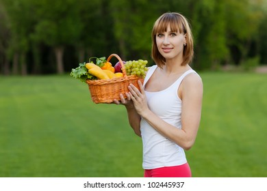 Young sportive woman with basket of fruits