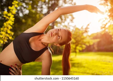 Young sportive woman doing exercises in summer park. Sportswoman stretching her body. Workout