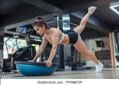 Young sportive woman leaning on bosu ball and lifting legs with great concentration.