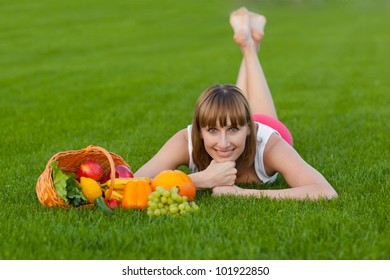 Young sportive woman lying on a grass with basket of fruits and vegetables