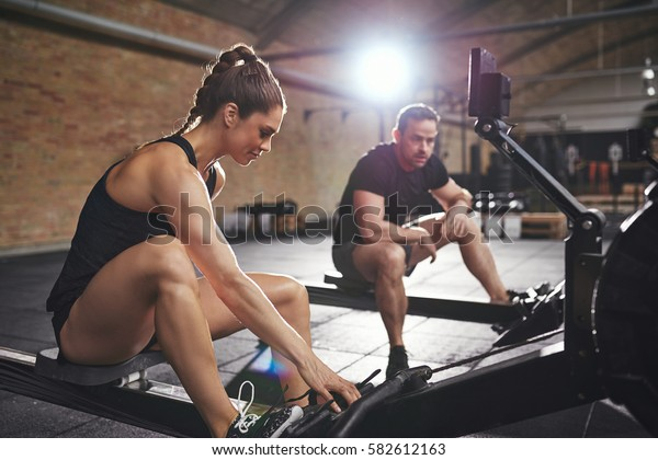 Young sportive woman and man sitting on rowing machines and having break.