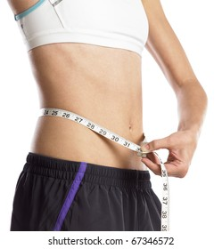 Young sportive woman measuring waist