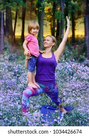 Young sportive woman practicing yoga with her little daughter in the violet madow