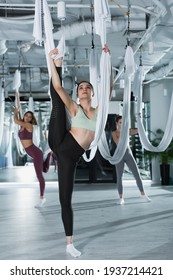 young sportive woman stretching leg with aerial yoga strap on blurred background