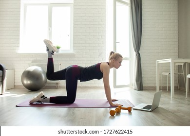 young sports girl do sports at home online with a laptop, sportswoman does exercise in the room, self-isolation concept