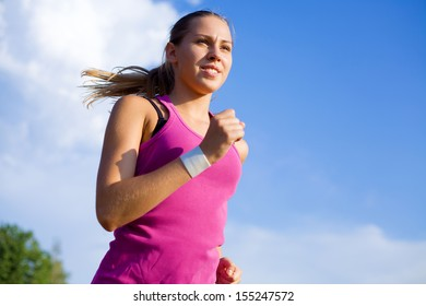 Young sports girl runs on a background of blue sky