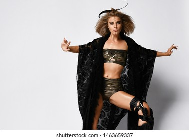 Young sports girl shaman in dark gold lingerie and a black cloak, with a bandage on her knee and feathers in her hair. Ritual dance, fighting capoera qigong