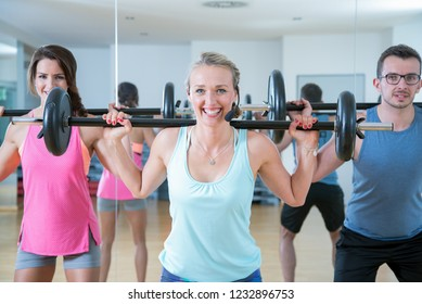 young sports group is training aerobics pump with barbell in the gym