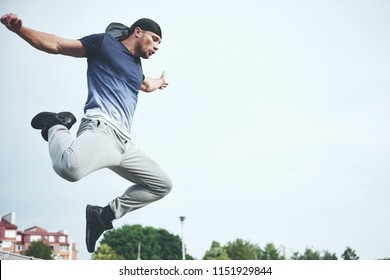 Young sports man doing parkour in the city