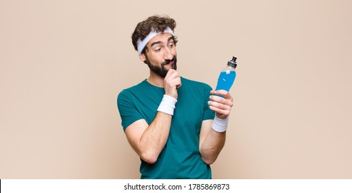 young sports man with an energy drink bottle against flat wall