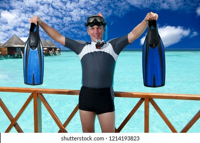 Young sports man with flippers, mask and tube near the sea. Maldives.