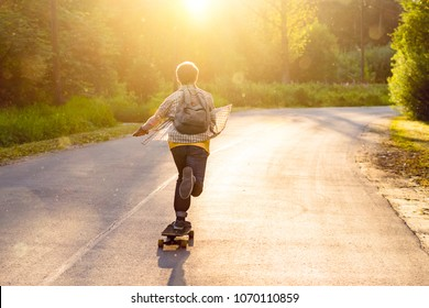 Young Sports Man skateboarding in the Park in Sunny summer morning. Healthy Lifestyle and Sport Concept. A man rides longbone, from behind. Freedom concept.