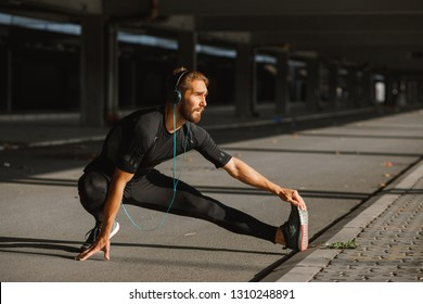 Young sports man stretching outdoors