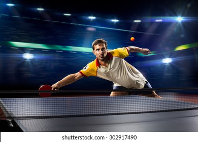 young sports man tennis player is playing on black background with lights