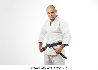 Young sports man in white kimono for sambo, judo, jujitsu posing on white background, looking straight, standing sideways