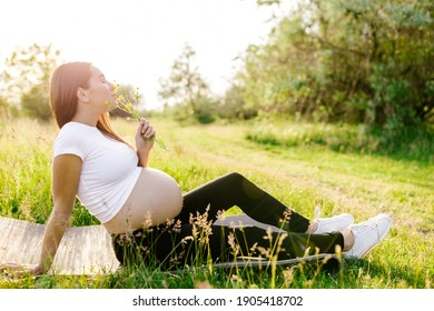Young sports pregnant girl sits on a sports mat on the grass in the fresh air and holds wildflowers in her hands. Outdoor recreation. Healthy pregnancy.