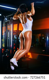 Young sports sexy brunette woman doing pull-ups in dark red gym interior
