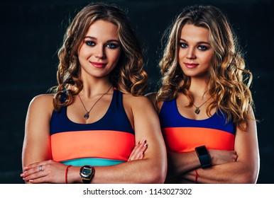Young sports twins girls team portrait in dark interior