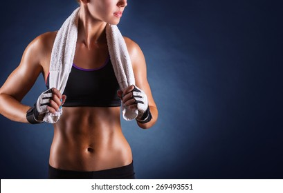 Young sports woman after workout with towel on his shoulders on a dark background
