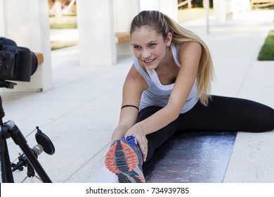 young sports woman blogger making a videos about gymnastic exercises in a public park