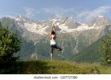 Young sports woman doing yoga on the green grass in the summer on the background of snowy mountains.